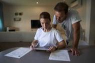 Teresa Reyes, junto a su pareja, José Fernández, revisan los informes médicos en el salón de su casa en Villanueva del Ariscal.