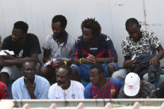 Migrants, some of whom disembarked from Spanish rescue ship Open <HIT>Arms</HIT> NGO, are seen at the immigration centre on the southern Sicilian island of Lampedusa
