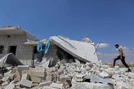 Un hombre camina encima de las ruinas de un edificio bombardeado en  Maaret al-Numan (Idlib).