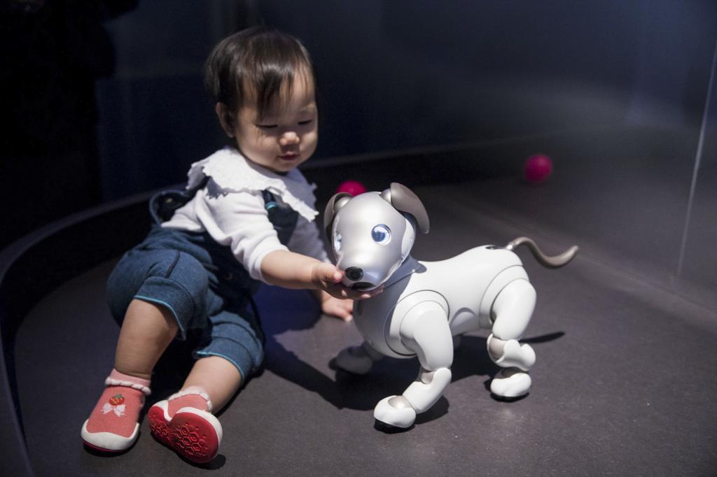 Una niña juega con un robot en forma de perro en la exposición.
