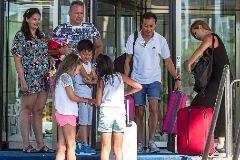 Un grupo de turistas extranjeros sale con sus maletas de un hotel.