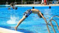 Un joven se zambulle en una piscina.|