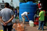 Decenas de habitantes de Ciudad de México llenan sus garrafas ante la escasez.