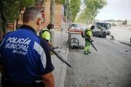 Un policía municipal vigila las labores de limpieza de los barrenderos municipalesen Alto de San Isidro, en Carabanchel, uno de los barrios conflictivos.