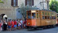 Turistas salen de la estación del Tren de Sóller y esperan para subir al tranvía. G.M.