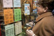 Una mujer mira publicidad sobre los viajes del imserso.