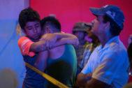 Dos jóvenes se abrazan frente al bar donde se desató el incendio.