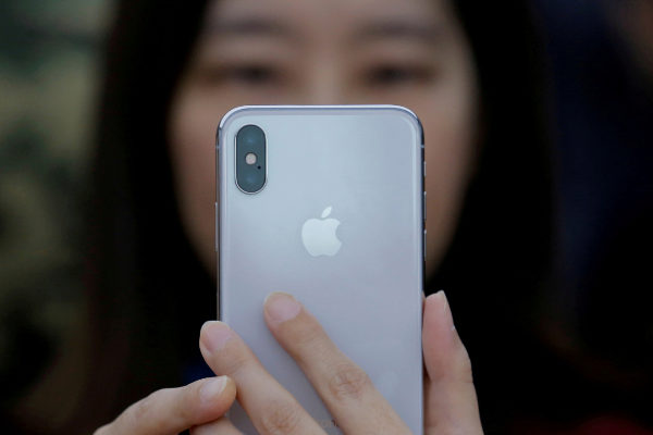 FILE PHOTO: A attendee uses a new iPhone X during a presentation for...
