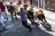 Corredor en el cuarto encierro de 'Sanse' perseguido por los toros
