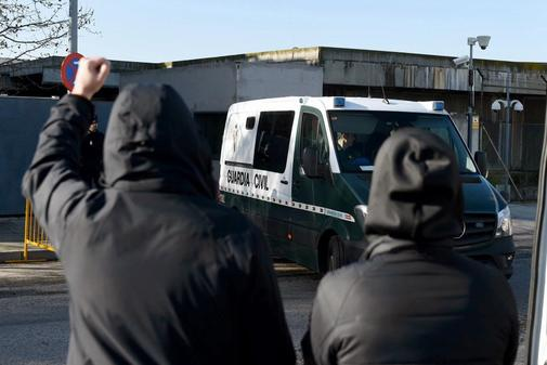 Dos personas reaccionan ante el paso de un furgón de la Guardia Civil...