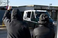 Dos personas reaccionan ante el paso de un furgón de la Guardia Civil durante el juicio en la Audiencia Nacional a los agresores de dos guardias civiles y sus parejas.