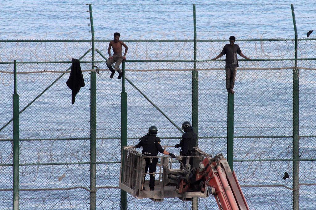 Dos inmigrantes subsaharianos se han encaramado a la valla fronteriza de Ceuta con Marruecos vigilados por la Policía.