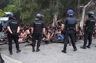 Agentes de la Policía vigilan a los inmigrantes que han llegado a Ceuta tras saltar la valla.