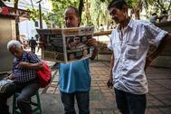Dos hombres leen en el periódico, en Medellín, la vuelta de 'Iván Márquez' a las armas.