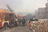 Bomberos de la Comunidad de Madrid remueven las pilas de fardos de papel en las labores de extinción.
