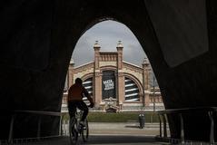 Un ciclista circula junto al centro cultural Naves del Matadero.