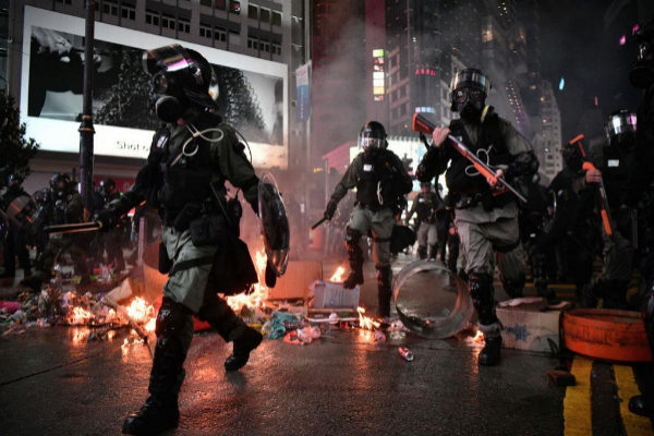 Policías armados entre barricadas ardiendo, este sábado en Hong...