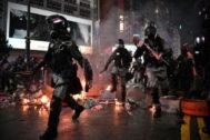 Policías armados entre barricadas ardiendo, este sábado en Hong Kong.