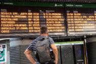 Un pasajero observa un panel informativo en la estación de Atocha.