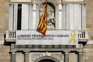 Vista del cartel reclamando la libertad de los líderes independentistas presos y un lazo amarillo en la fachada del Palau de la Generalitat horas antes de que venza el plazo de 24 horas que la Junta Electoral Central le ha dado para que ordene retirar los lazos amarillos de los edificios públicos catalanes, bajo advertencia de posibles responsabilidades penales.