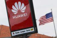Logotipo de la empresa china de tecnología móvil <HIT>Huawei</HIT> junto a una bandera de EEUU.