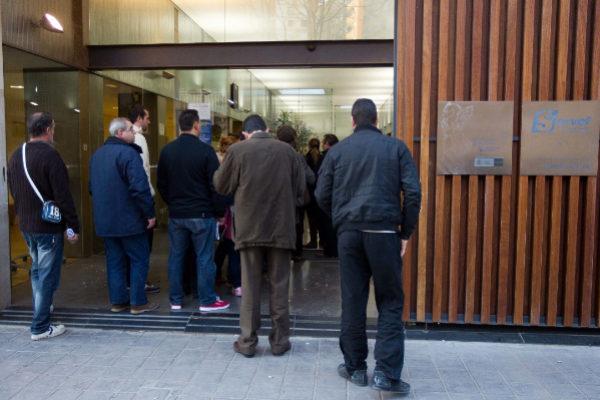Varias personas hacen cola en las puerta de la oficina del INEM.