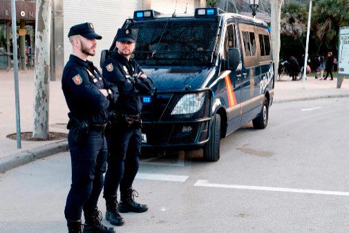 Dos agentes del Cuerpo Nacional de Policía, frente a un furgón.