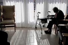 Un anciano sentado en una residencia.