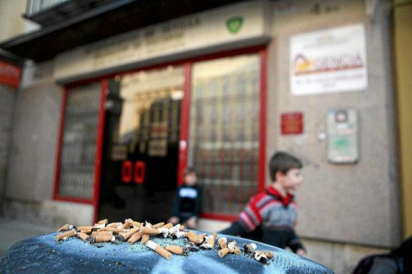 Un niño pasa ante un cenicero lleno de colillas en una calle de...