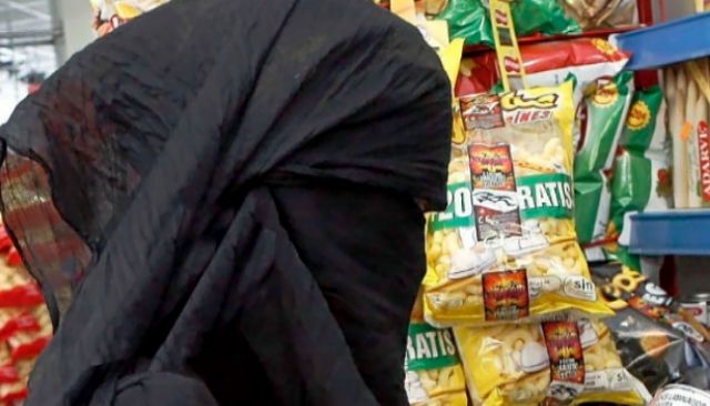 Una mujer con burka en un comercio en Málaga.