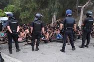 Agentes policiales custodian a los inmigrantes llegados de forma ilegal a Ceuta el pasado viernes.