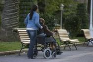 Una mujer pasea a una persona mayor en silla de ruedas en Bilbao.