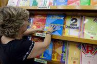 Una librera coloca los libros de texto en una estantería.