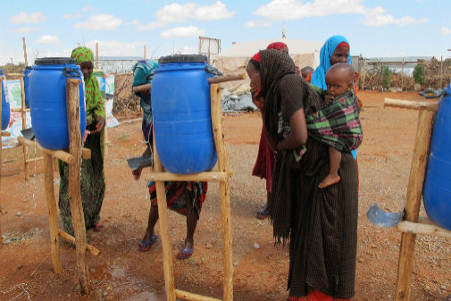Mujeres etíopes con sus hijos recogen agua en un campo de refugiados.