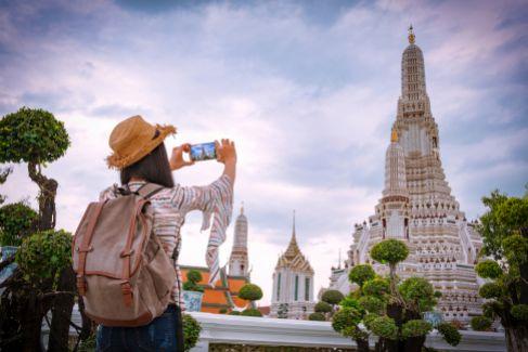Una mujer toma una foto del Wat Arun o Templo del Amanecer.