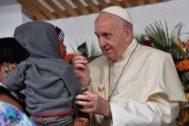 El Papa Francisco ofrece un regalo a un niño en brazos de su madre, en Maputo.