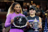 == FOR NEWSPAPERS, INTERNET, TELCOS & TELEVISION USE ONLY == NEW YORK, NEW YORK - SEPTEMBER 07: Bianca <HIT>Andreescu</HIT> (R) of Canada celebrates with the championship trophy alongside runner up Serena Williams (L) of the United States during the trophy presentation ceremony after the Women's Singles final on day thirteen of the 2019 US Open at the USTA Billie Jean King National Tennis Center on September 07, 2019 in the Queens borough of New York City. Elsa/Getty Images/AFP