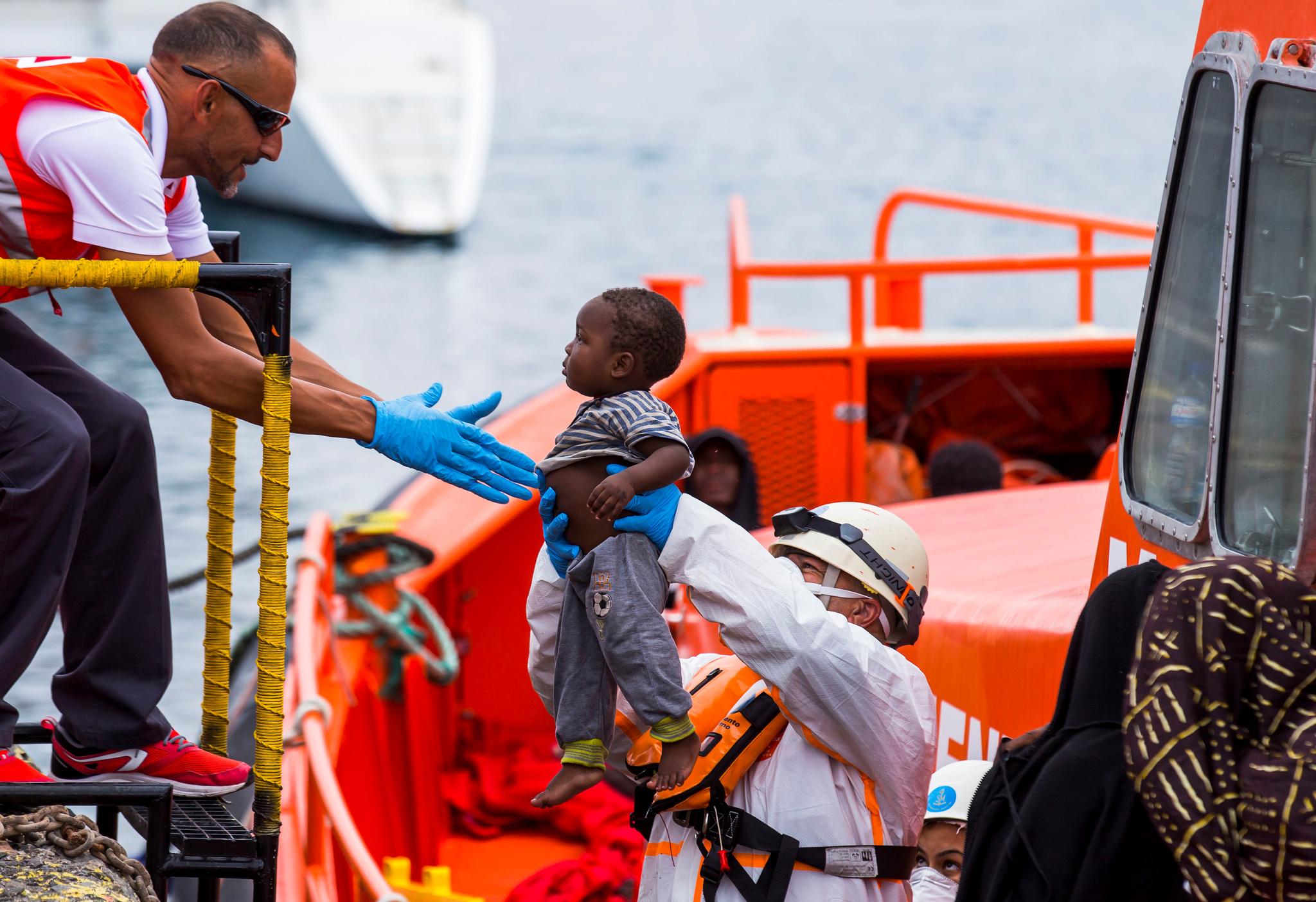 Un bebé es evacuado de una embarcación en el Muelle de Arguineguín...