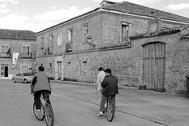 Unos jóvenes, montando en bici en un pueblo en una imagen antigua.