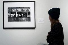 Una mujer mira una de las fotografías de Robert Frank.