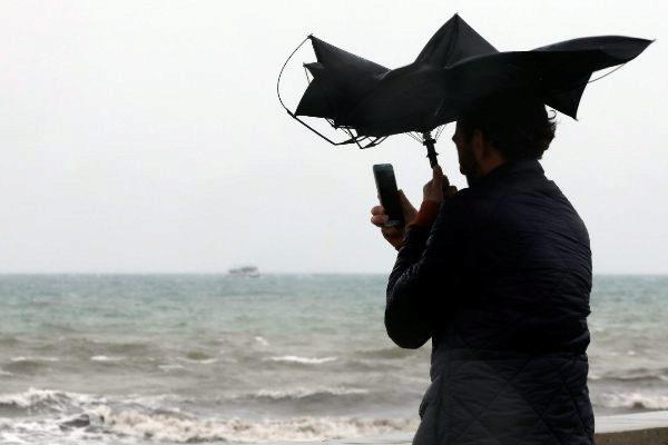 Una persona se hace una fotografía en la Playa de la Malvarrosa de Valencia bajo la lluvia.