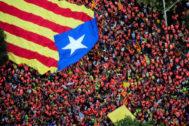 Miles de manifestantes portan una enorme estelada en la Diada de 2018 en Barcelona.
