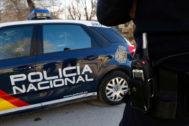 Un agente junto a un coche de la Policía Nacional.