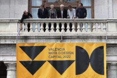 Ribó, Puig y los organizadores de València Capital Mundial del Diseño despliegan el cartel del evento en el vbalcón del Ayuntamiento.