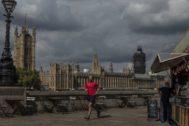 Un hombre corre por el Tamesis frente a Westminster.