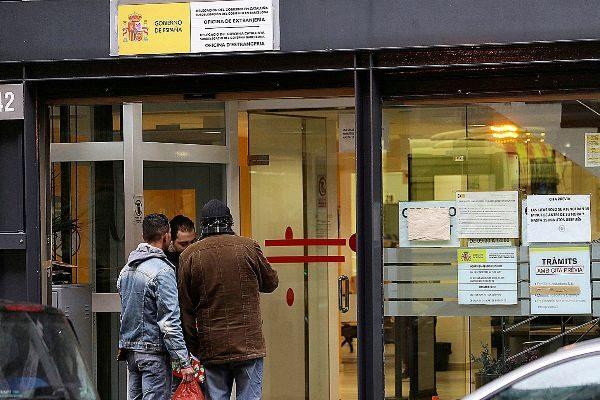 Tres hombres ante una Oficina de Extranjería en Barcelona.