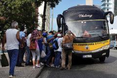 Cubanos intentan subir a uno de los pocos autobuses que circulan por La Habana.