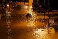 Un coche se atasca en una calle inundada por las lluvias torrenciales que azota Orihuela