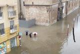 Vecinos de Orihuela caminan por una calle inundada de la ciudad.