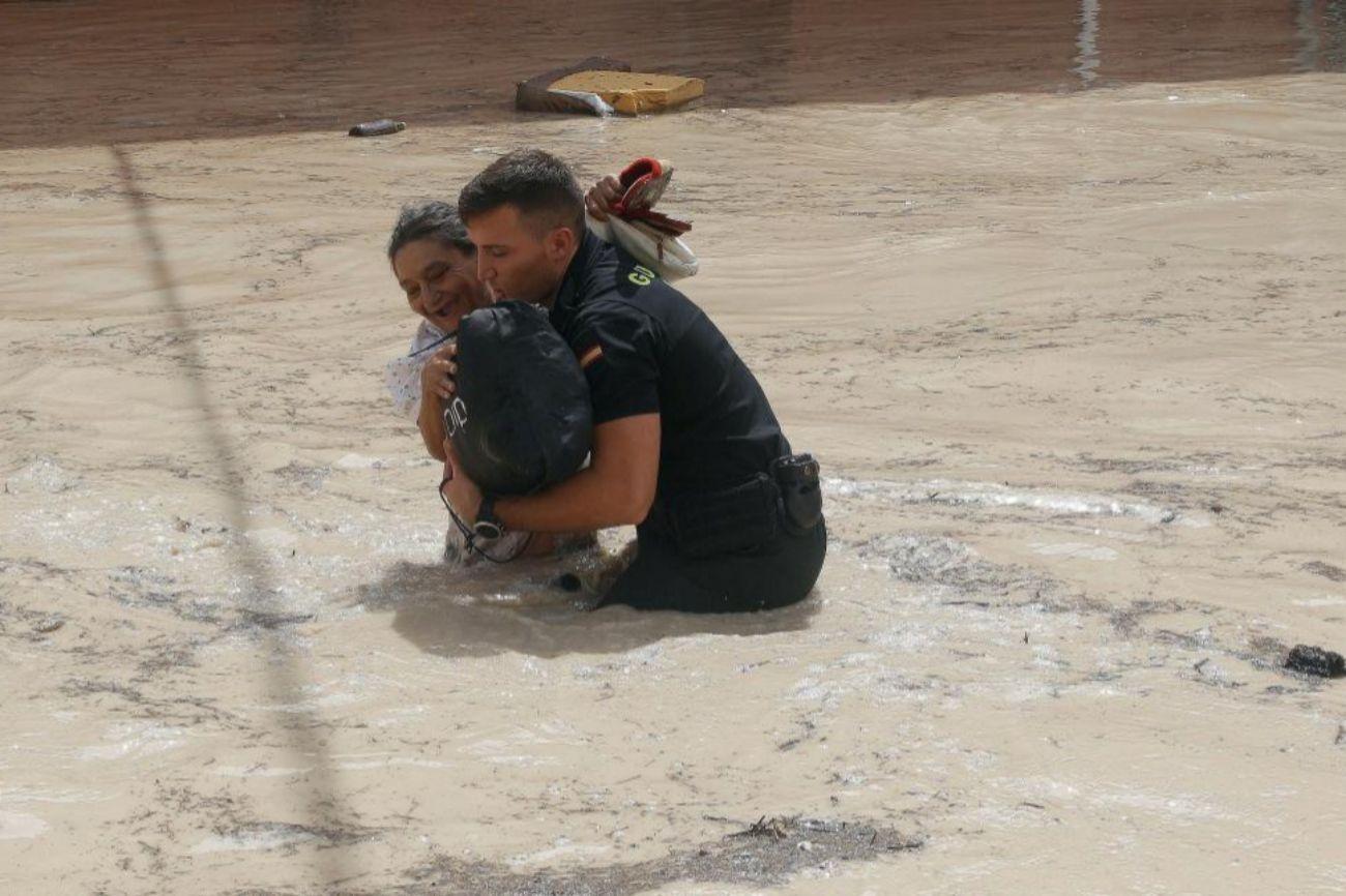Un policía ayuda a una vecina de Almoradí este viernes tras la...